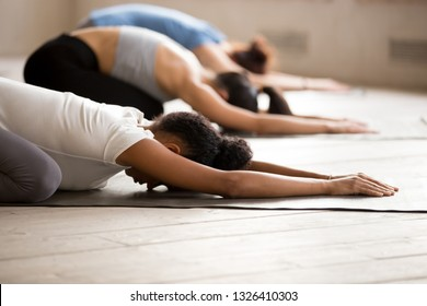 Group of diverse young sporty people practicing yoga, doing Child exercise, Balasana pose, working out indoor close up, mixed race female students training at club studio. Well being, wellness concept