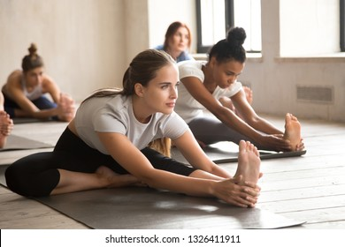 Group of diverse young sporty people practicing yoga lesson doing Head to Knee Forward Bend exercise, Janu Sirsasana pose, working out, indoor, mixed race students training at sport club or studio