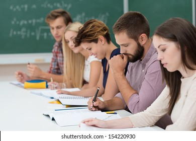 Group of diverse young students at work in the classroom sitting at a long table working on their notes and studies