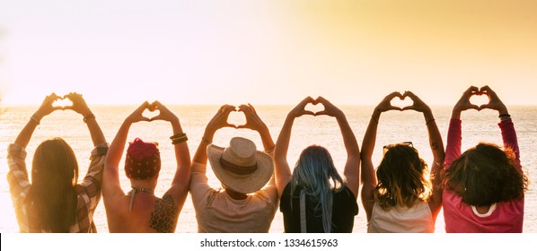 Group of diversity alternative young woman enjoying the sunset at the sea doing hearth symbol with hands - people enjoying friendly lifestyle - vacation in friendship concept for females