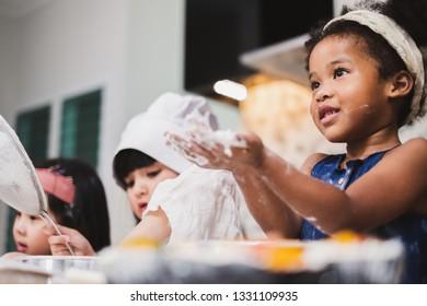 Group diversity kids girl making cake bakery in kitchen