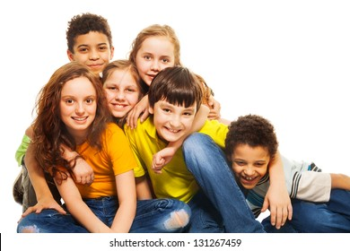 Group of diversity looking kids, boys and girls sitting on the floor hugging and laughing