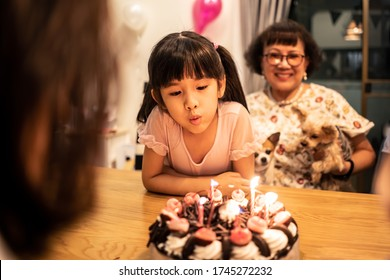 Group of diversity people in big family, young children and old parents have fun celebrate happy birthday anniversary party together at home. Little girl blowing out candles on ice cream cake on table
