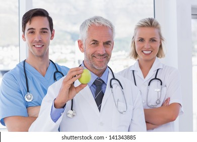 Group of doctor and nurses standing while one is holding a green apple