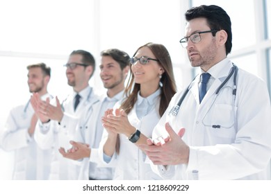 group of doctors applauds, standing in the hospital
