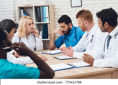 A group of doctors from different races is meeting at a table. They are in the clinic. They discuss the results of the patient's tests. They have a medical consultation.