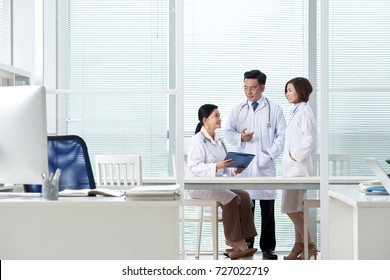 Group of doctors discussing work in office
