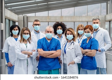 Group of doctors with face masks looking at camera, corona virus concept. - Shutterstock ID 1641184876