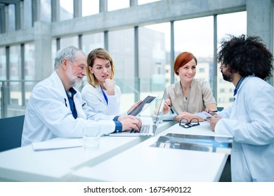Group of doctors with laptop on conference, medical team discussing issues.