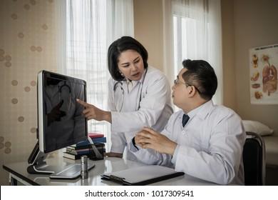 Group of doctors looking at computer on meeting at hospital ward.
