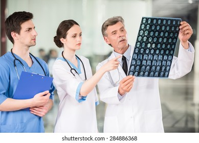 Group of doctors looking at X-ray at offie.