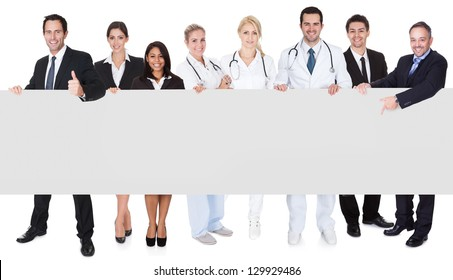 Group of doctors and managers presenting empty banner. Isolated on white