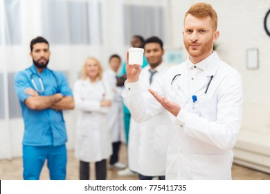 A group of doctors are posing for the camera. They stand in a bright medical office. They are all different nationalities. Doctors work together in one hospital.