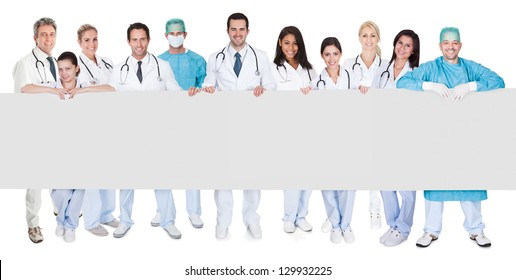 Group of doctors presenting empty banner. Isolated on white