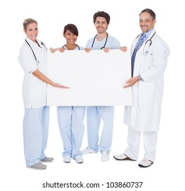 Group of doctors presenting empty board. Isolated on white