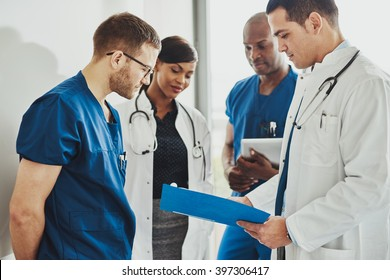 Group of doctors reading a document in meeting room at hospital