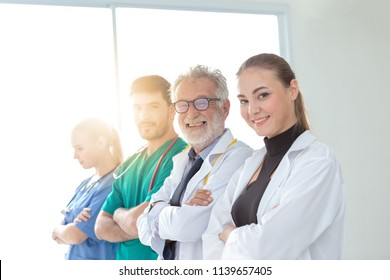 A group of doctors are using a digital tablet for discussing diagnosis and smiling while standing in front of his patient.