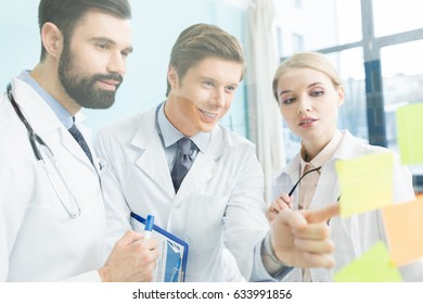 group of doctors in white coats having work meeting in clinic