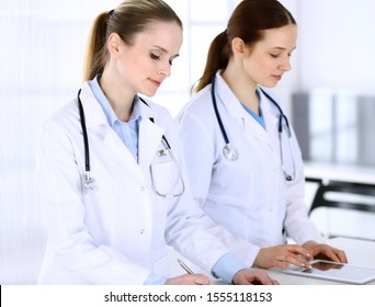 Group of doctors at work in hospital. Physician filling up medical documents or prescription while standing at reception desk. Data in medicine and health care concept