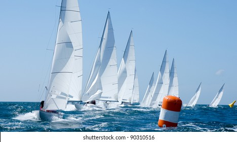 group of dragon yacht sail in regatta near a  buoy