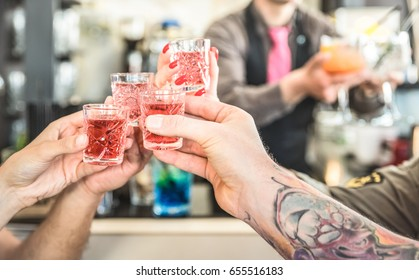 Group of drunk friends toasting cocktails at bar restaurant - Food and beverage concept on nightlife moments - Defocused bartender serving drinks on background - Focus on hands cheering red shot glass