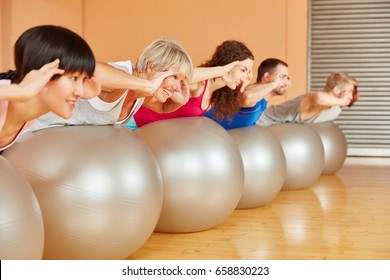 Group during back training in pilates class at fitness center