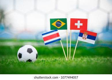 Group E - National Flags of Brazil, Switzerland, Costa Rica, Serbia. Flags on green grass on football stadium