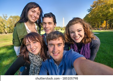Group of early and middle 20s aged friends on a road trip to the nations capital takes a selfie (self portrait) with the Washington Monument in the background.