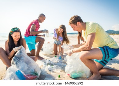 Group of eco volunteers  holding bags with plastic after sorting waste - Friends cleaning the beach and collecting plastic to save marine life