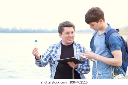 Group of ecologists. Analysis of water pollution taken from the reservoir. The teacher and the student are studying the water sample. Practical lesson.