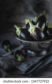 Group of eggplant with water drops in a metal colander on a wooden table.