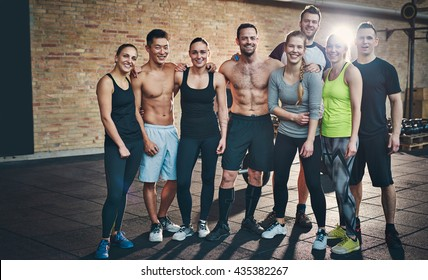 Group of eight athletic young female and male adults standing together as good friends in gym after a difficult workout session