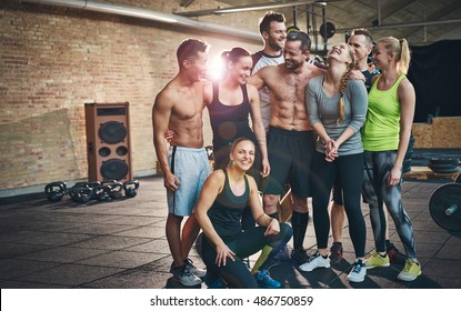 Group of eight happy muscular female and male adults standing together as good friends in gym with large speaker in background after a difficult workout session