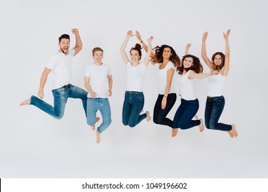 Group of elated vivacious barefoot young friends wearing jeans and white tops leaping in the air and cheering isolated on white