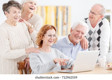 Group of elderly active people looking at laptop screen while watching photos from the old days and reminiscing about the past