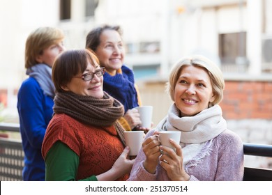 Group of elderly female friends drinking tea at balcony and smiling. Focus on blonde
