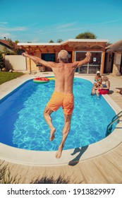 Group of elderly friends relaxing and sunbathing by the swimming pool on a hot summer day, one man having fun jumping into the pool while on a vacation