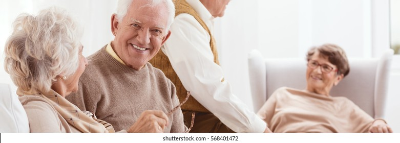 Group of elderly friends spending time together in a living room