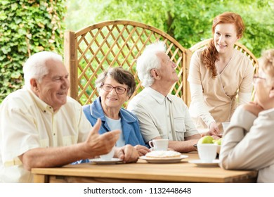 Group of elderly pensioners enjoying their time together by a table outside in a garden of a retirement home. Young caretaker assisting.