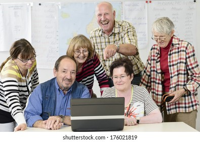A group of elderly people behind a laptop.