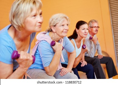 Group of elderly people doing senior sports in fitness center with dumbbells