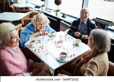 Group of elderly people sitting by table, talking and playing lotto