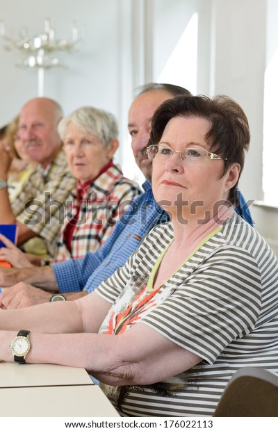 A group of elderly people are sitting in a classroom.