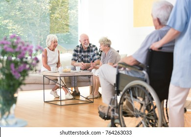 Group of elderly people sitting on the sofa during lunch time in common room