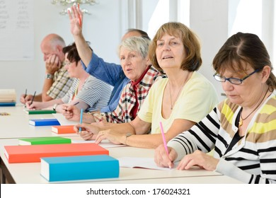 A group of elderly people sitting together at a table with books.
