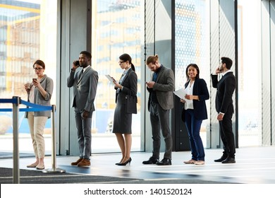 Group of elegant employees in suits standing in queue by blue ribbon while waiting for registration and check-in
