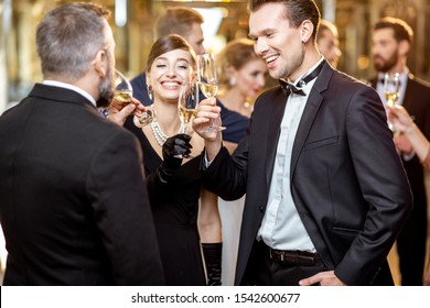 Group of elegant people well-dressed in retro styles hanging out together, having fun with drinks at the luxury restaurant during the grand celebration