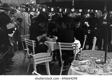 Group of elegant women sitting at table set outdoors in front of crowd of people