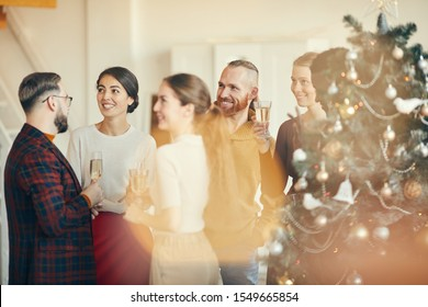 Group of elegant young people mingling and drinking champagne during Christmas party in beautiful house, copy space