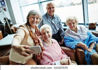 Group of elegant-looking senior people taking selfie with modern smartphone while enjoying each others company in pretty small cafe